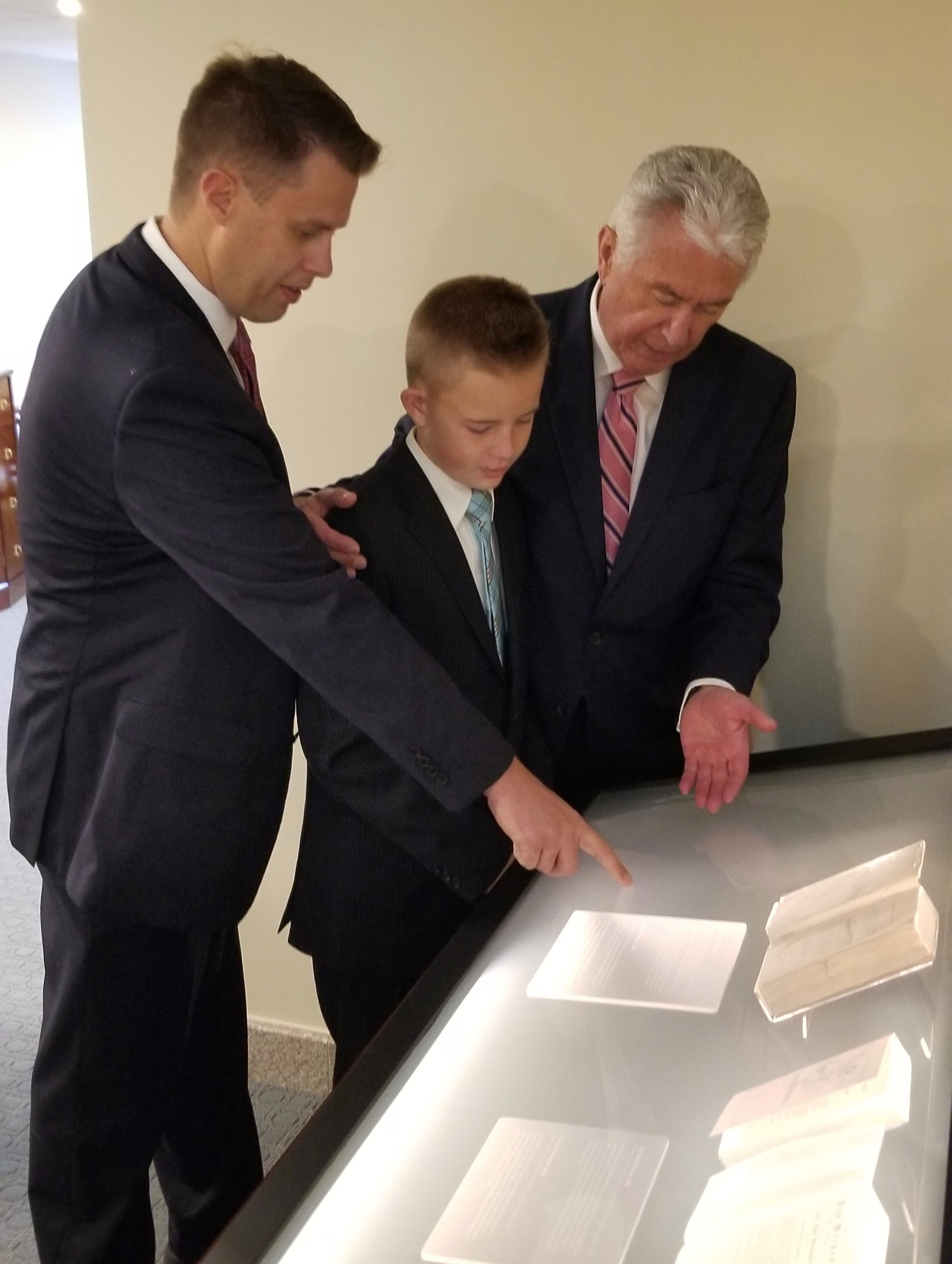 James Burton, left, and his son Gavin look with Elder Dieter F. Uchtdorf at the first-edition Book of Mormon donated by the family of the late Elder Theodore M. Burton, who had presided over the West German Mission and had encouraged a young Dieter Uchtdorf to remain and raise a family in Germany rather than relocated to the United States.