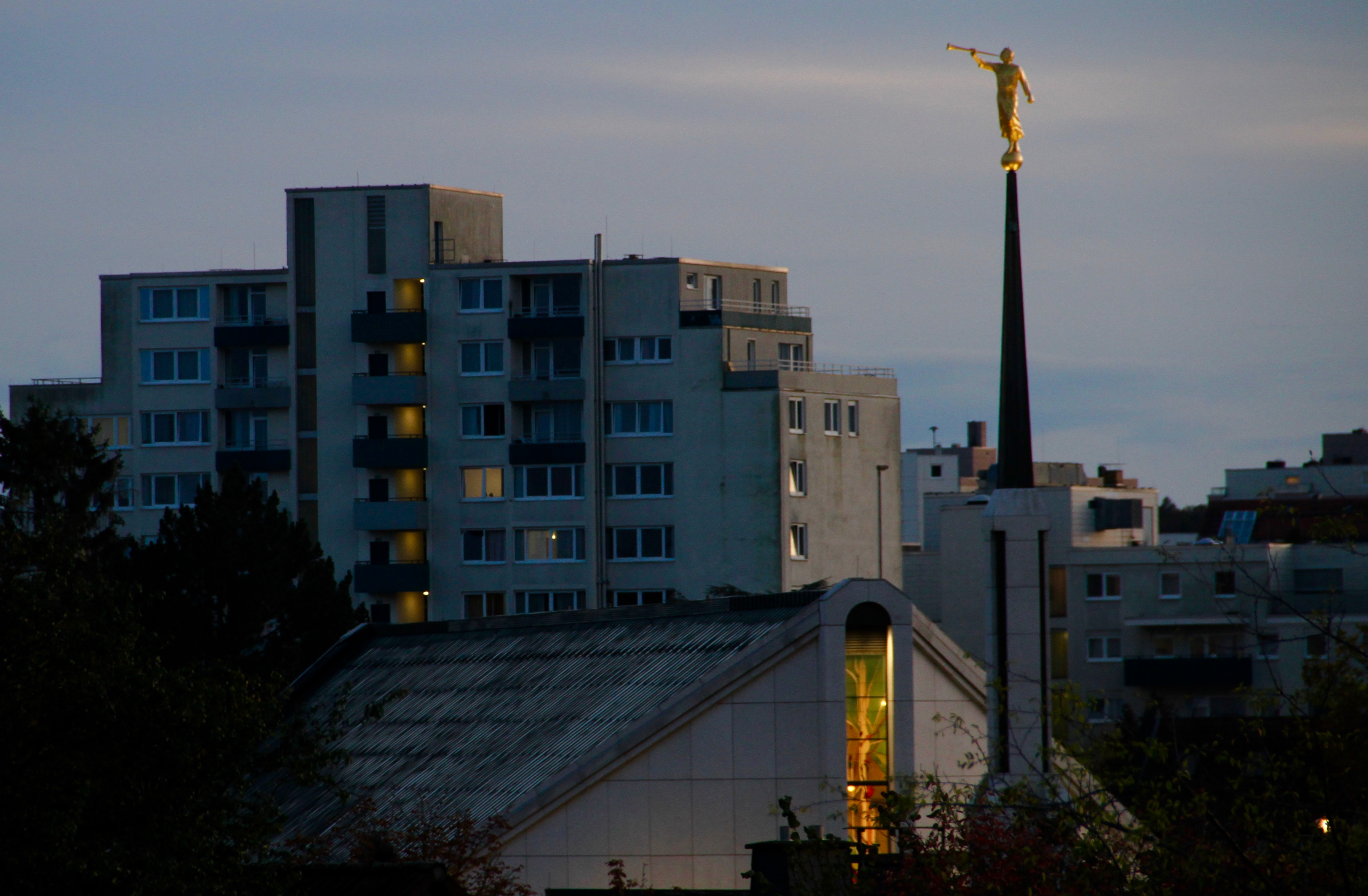 A long-distance view of the Frankfurt Germany Temple and spirt in front of neighboring buildings in Friedrichsdorf, Germany, at dusk on Oct. 18, 2019.