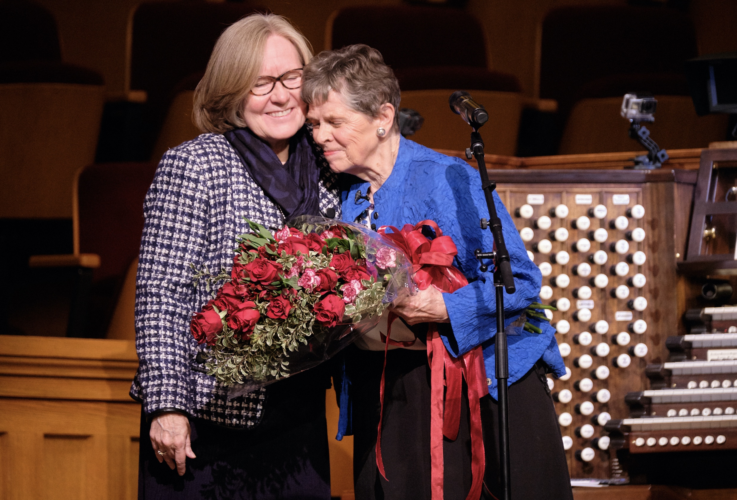 Retiring Temple Square organist Bonnie Goodliffe accepts a bouquet of red roses from Tabernacle Choir office volunteer Susan Empey at the Salt Lake Tabernacle after 40 years of service on Monday, Oct. 21, 2019.