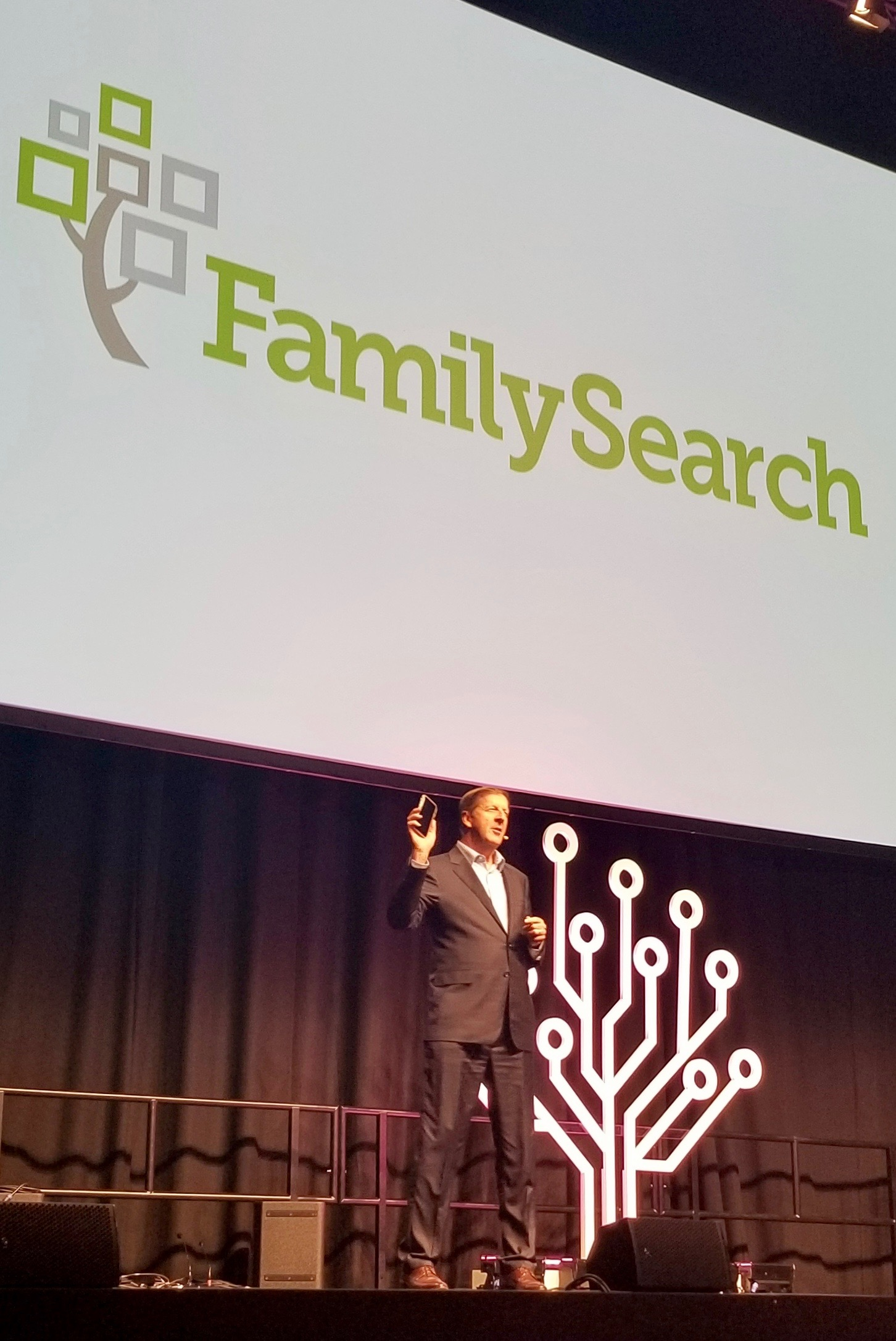FamilySearch CEO Steve Rockwood holds a cellphone as a reminder of the Family Tree app while speaking during RootsTech London in the London ExCel auditorium on Thursday, Oct. 24, 2019.