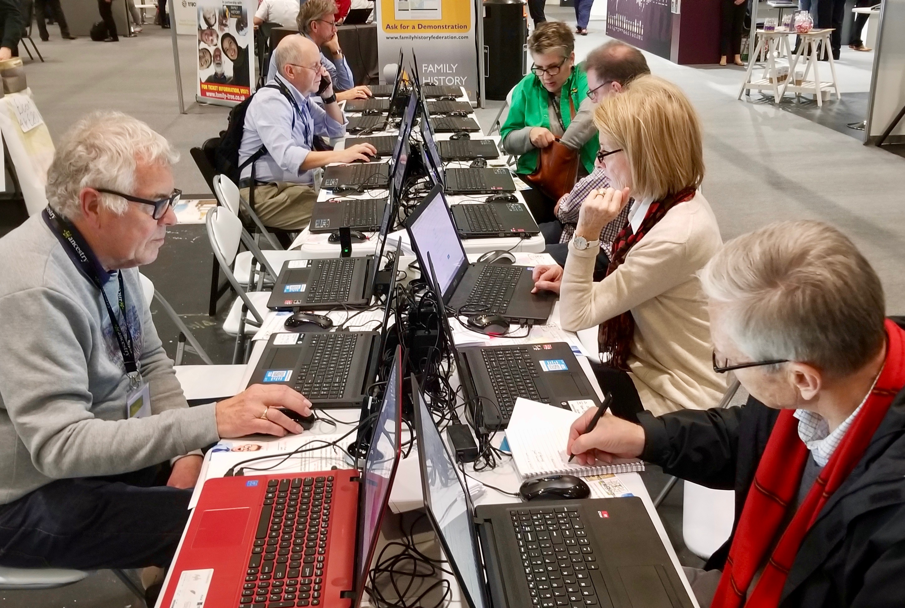 RootsTech London attendees work at a bank of laptops in the exhibition hall of the London ExCel on Friday, Oct. 25, 2019.