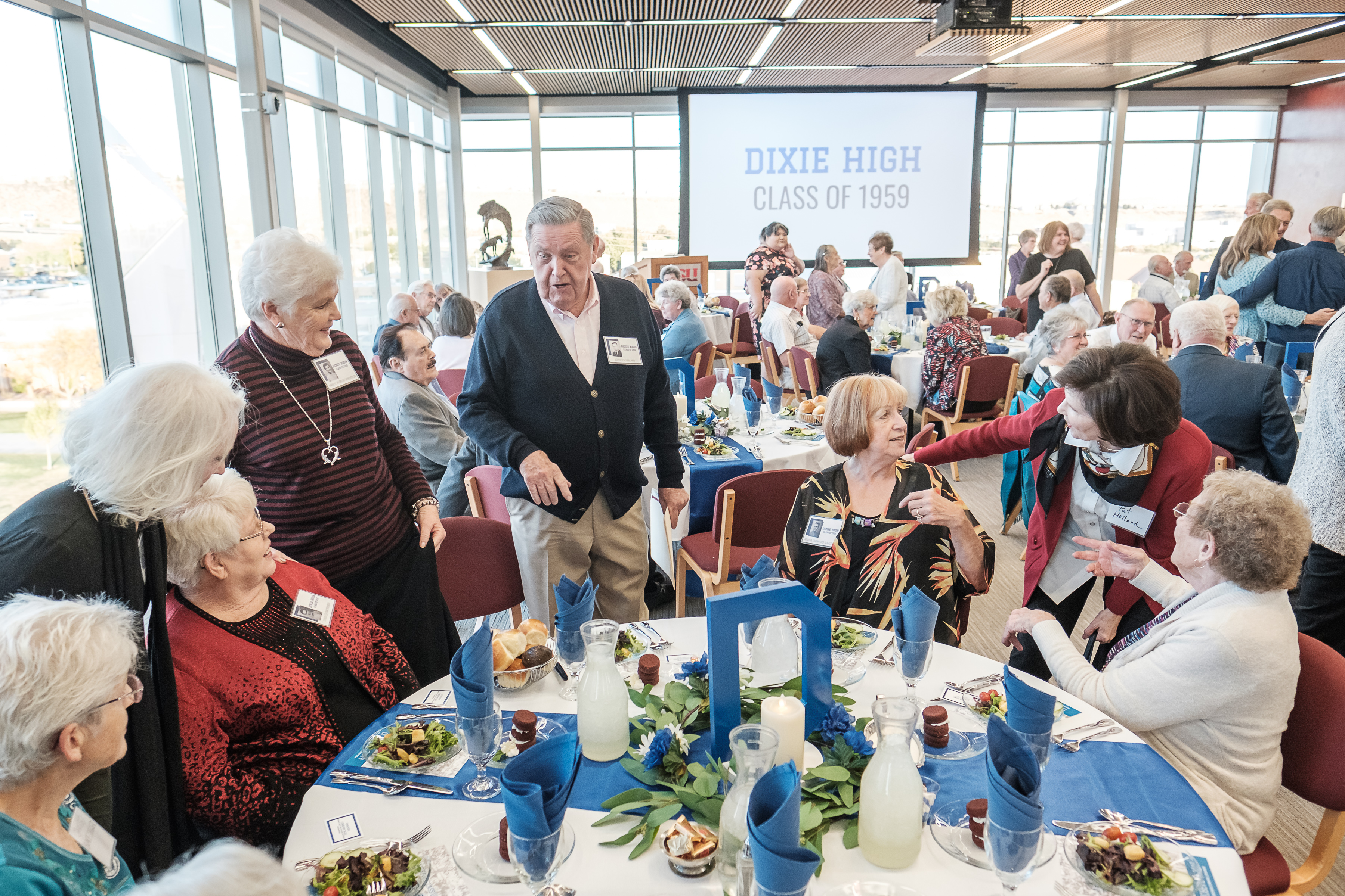 Elder Jeffrey R. Holland, standing center left, a member of the Quorum of the Twelve Apostles of The Church of Jesus Christ of Latter-day Saints, and his wife, Patricia Holland, second from right, greet a table of classmates and guests at the 60-year reunion for the Dixie High School class of 1959 on Thursday, Oct. 24, 2019, in St. George.