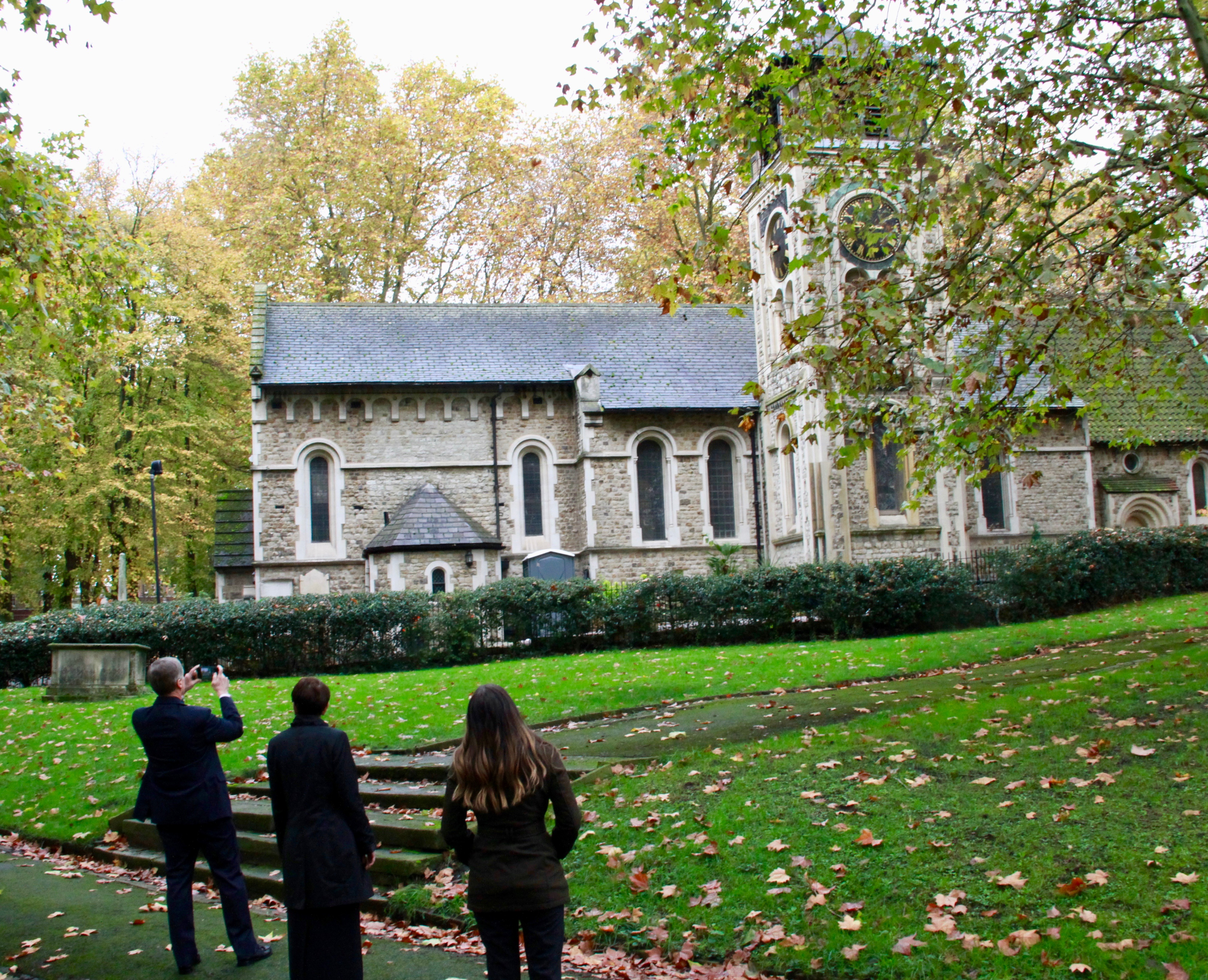 Elder David A. Bednar takes a photo of the St. Pancras Old Church on Oct. 25, 2019, in London. He's joined by Sister Susan Bednar, center, and Whitney Peterson, a FamilySearch content strategist specializing in the British Isles, right.