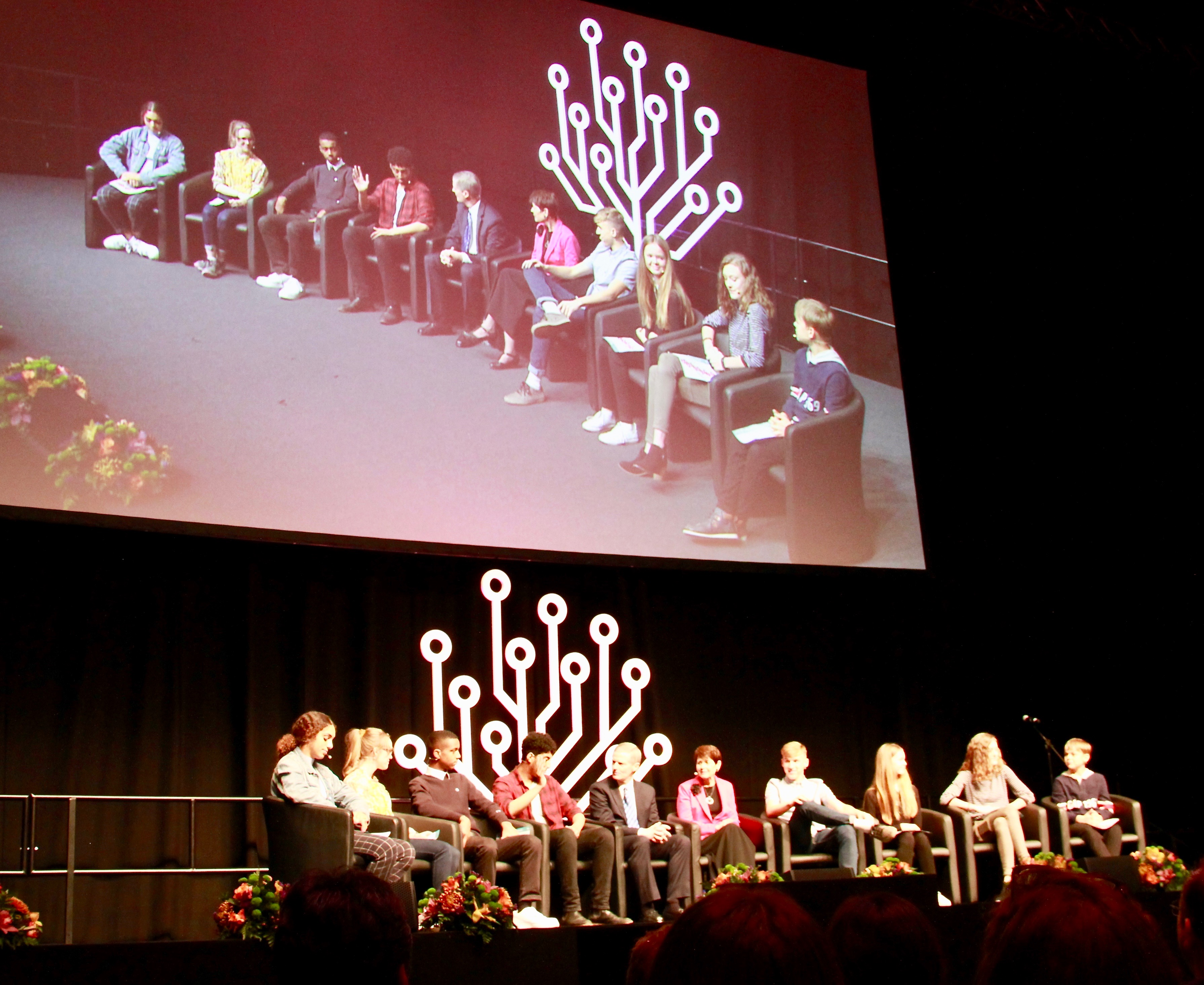 "Eight young people participate in the ""Youth Experience"" panel discussion with Elder and Sister Bednar during RootsTech London on Saturday, Oct. 26, 2019."