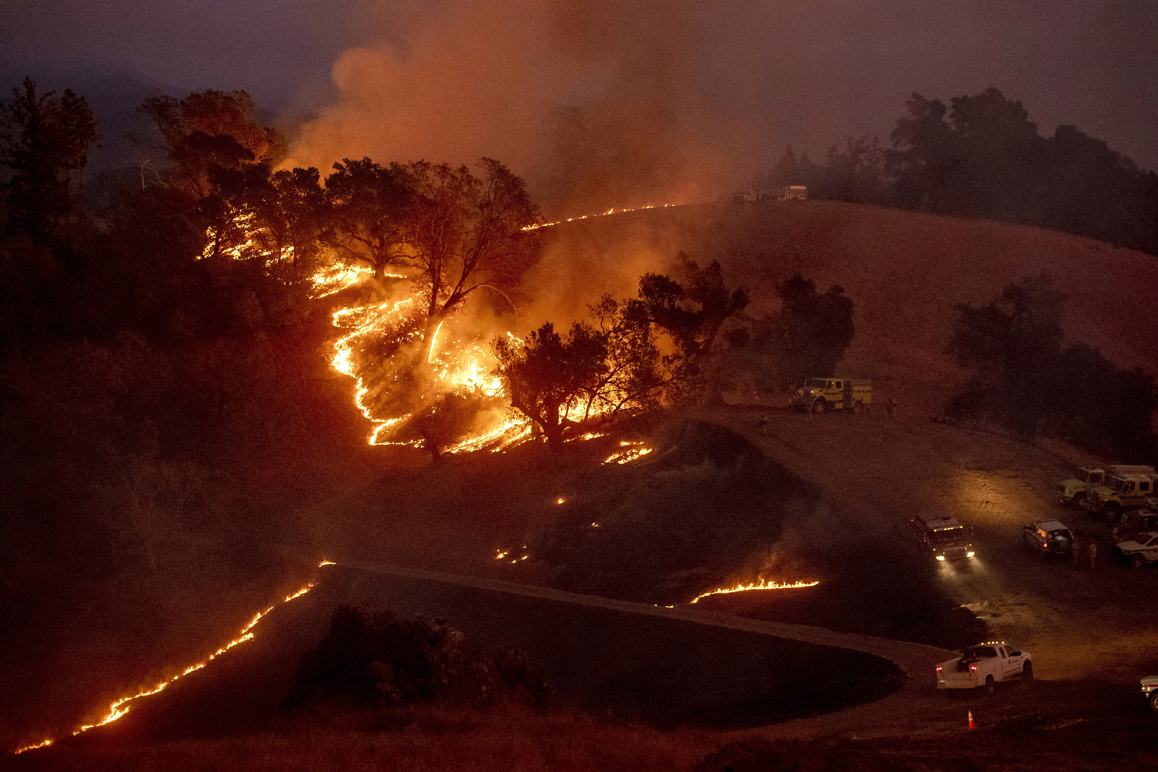 Flames from a backfire, lit by firefighters to slow the spread of the Kincade Fire, burn a hillside in unincorporated Sonoma County, Calif., near Geyservillle on Saturday, Oct. 26, 2019. Authorities are fighting a Northern California blaze that forced evacuation orders and warnings for nearly all of Sonoma County stretching to the coast, with forecasts of strong winds prompting officials to start cutting electricity for millions of people in an effort to prevent more fires. (AP Photo/Noah Berger)