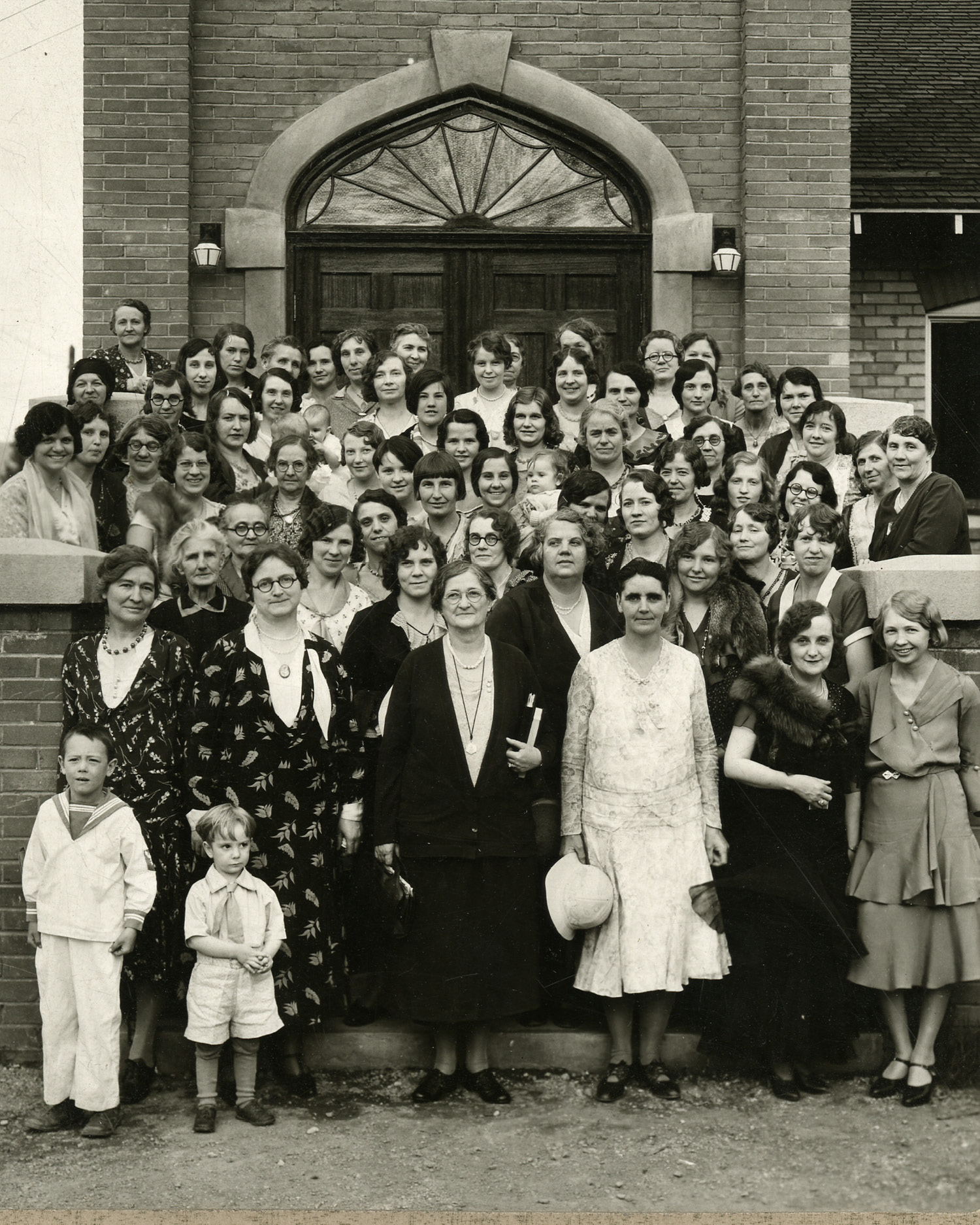 Sister Amy Brown Lyman at Social Service Training in Anaconda, Montana, circa 1920. Lyman, bespec- tacled in the center of the front row, became a trained social worker after formative visits to Hull House in Chicago and was a leader in implementing social service work within the Relief Society. Sister Lyman served on the Relief Society general board for 36 years, including her time as president. Photograph by Montgomery Studio.