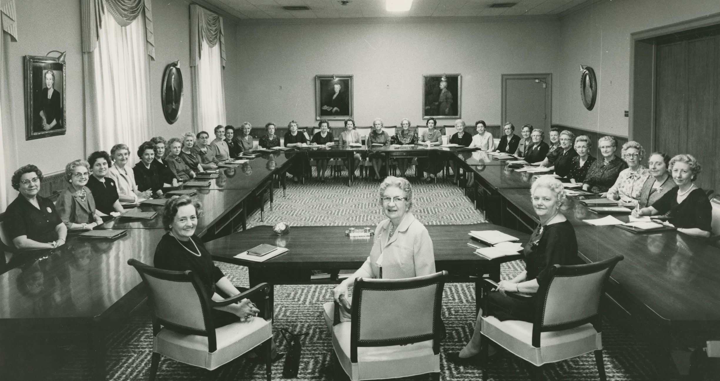 Sisters Belle S. Spafford, Marianne C. Sharp and Louise W. Madsen with the Relief Society general board in 1962, with members of the presidency at the head of the table. Left to right: Sisters Madsen, Spafford and Sharp, the Relief Society general board poses in the 6-year-old Relief Society Building. Board members trained Relief Society units throughout the world, oversaw temple clothing production, published the Relief Society Magazine, and created Relief Society curriculum. Photograph by J. M. Heslop.