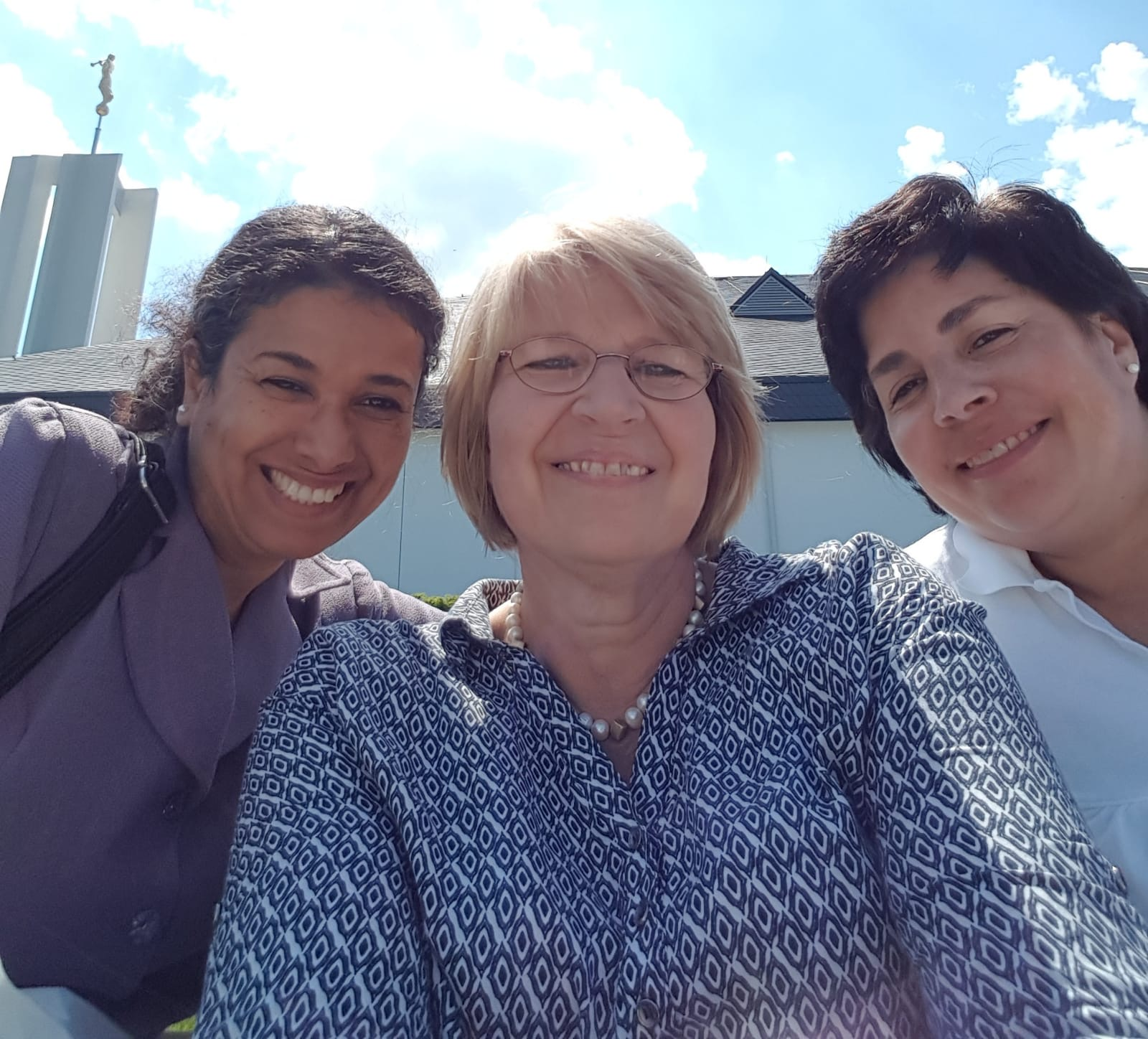 Three sisters of the Friedrichsdorf Germany Stake pause for a selfie outside the Freiberg Germany Temple during their May 2018 temple trip.