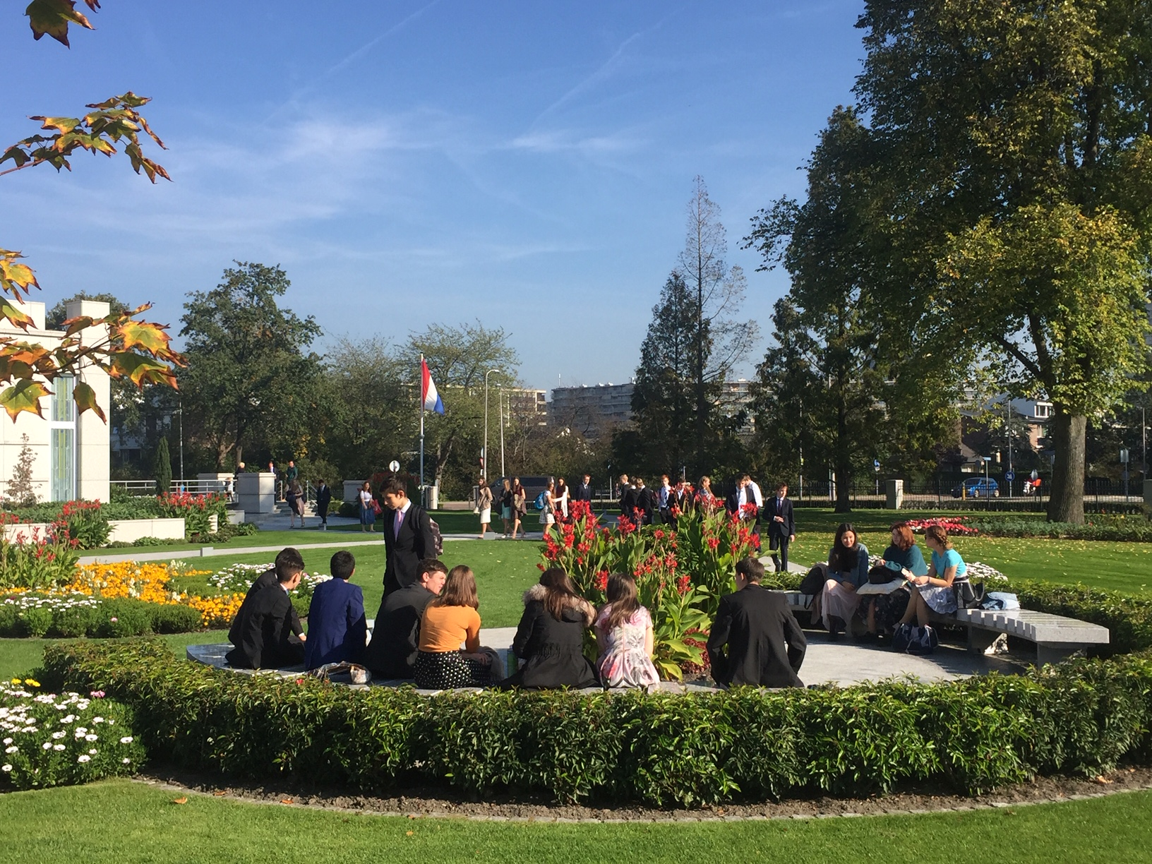 Youth from the Friedrichsdorf Germany Stake sit on the grounds of The Hague Netherlands Temple during the stake's October 2018 temple trip.