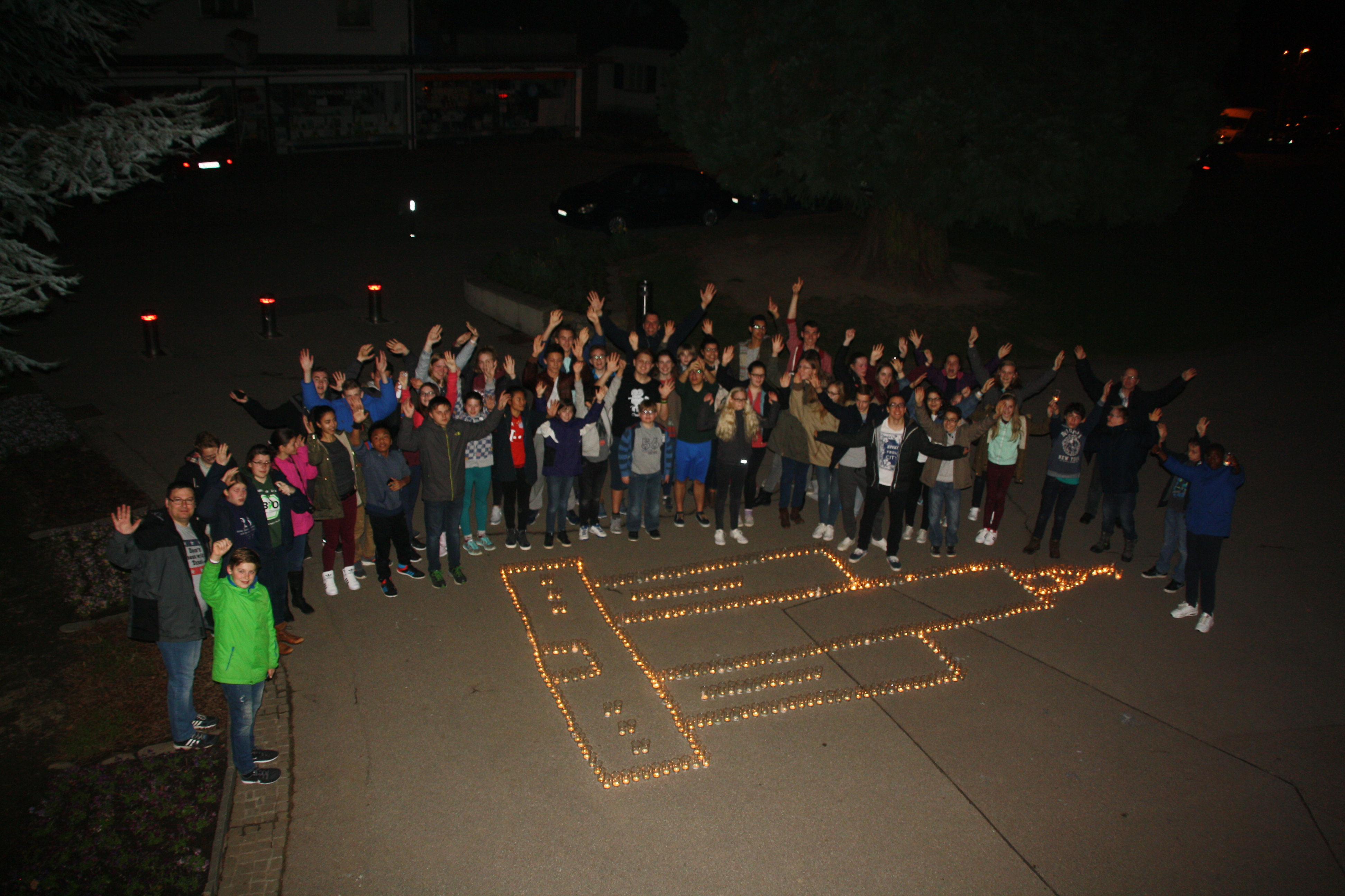 Youth of the Frankfurt Germany Stake gather for a group photo beside a candle-created image of the temple during an annual stake youth temple camp in Freiberg, Germany.