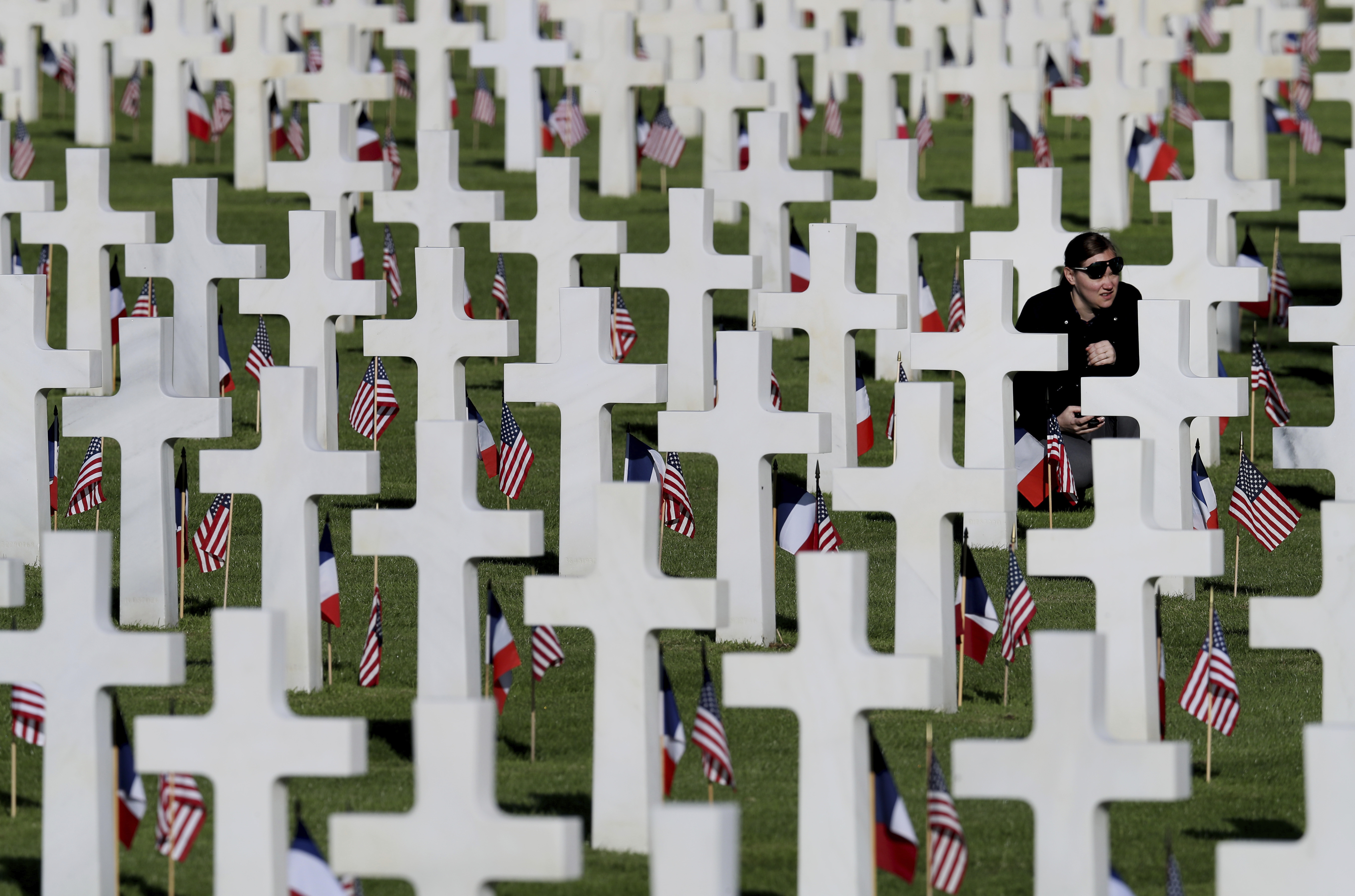 A young woman visits headstones of World War II soldiers prior to a ceremony to mark the 75th anniversary of D-Day at the Normandy American Cemetery in Colleville-sur-Mer, Normandy, France, Thursday, June 6, 2019. (David Vincent, Associated Press)