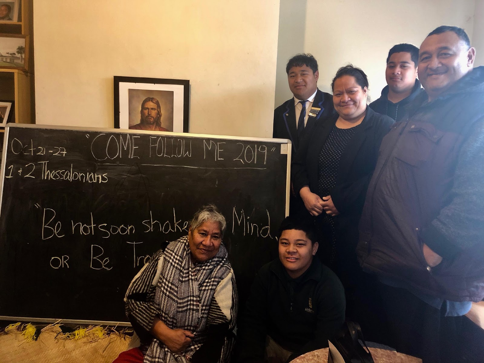 "A family in Christchurch, New Zealand, poses with the blackboard they use to plan their weekly ""Come, Follow Me"" lessons. Sister Sharon Eubank visited the family during a trip to the Pacific Area of the Church with Sister Craven in October 2019."