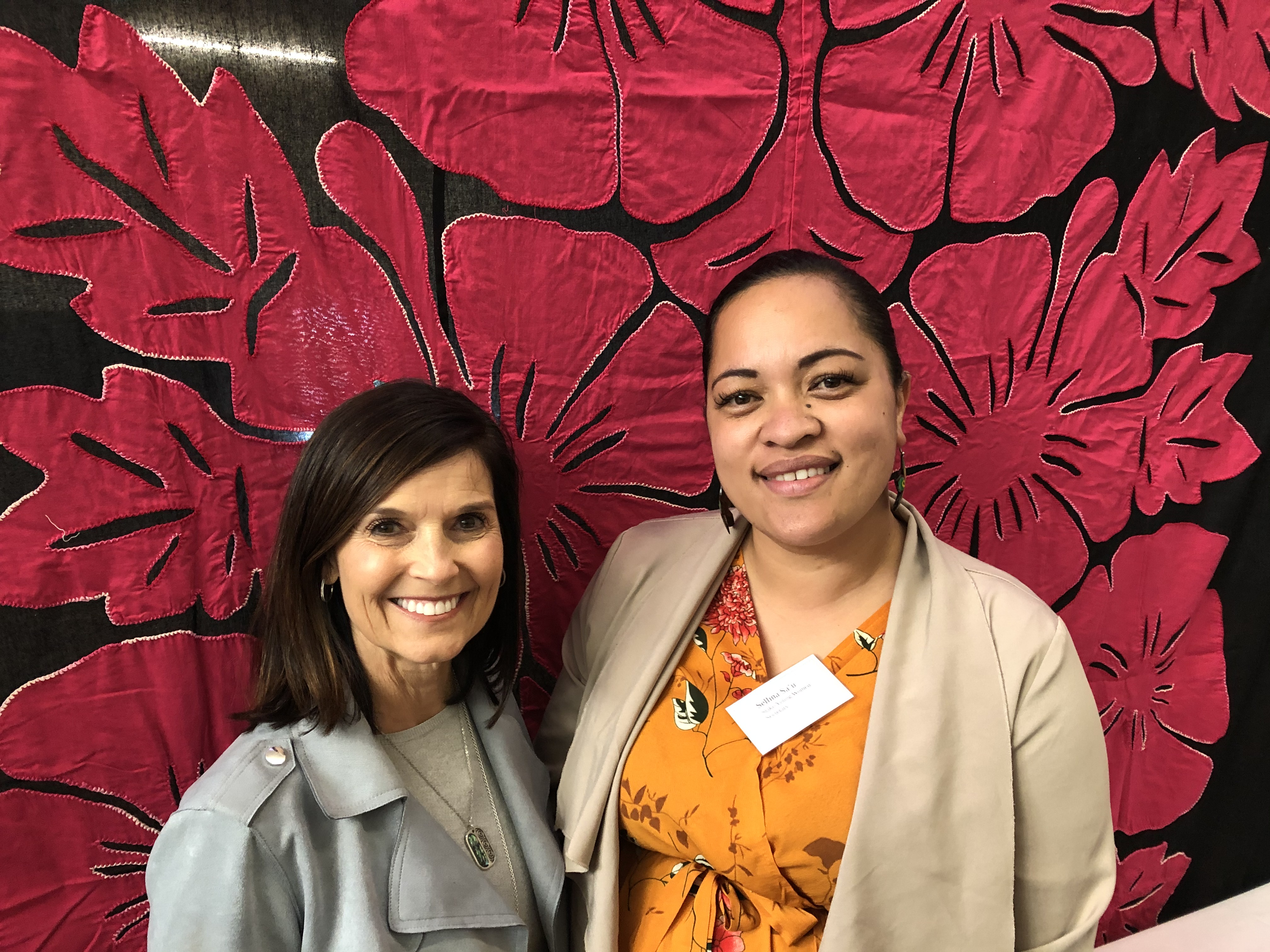 Sister Becky Craven, left, poses with a Church member in Dunedin, New Zealand, in front of a traditional Maori quilt during a visit to the Pacific Area in October 2019.