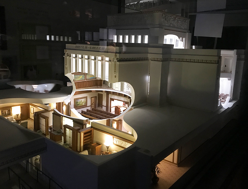 A simulated night view of the Laie Hawaii Temple model, with the cut-away windows showing a portion of the foyer in the foreground and the assembly room chapel above. The Laie Hawaii Temple is designed for progressive endowment ceremonies.