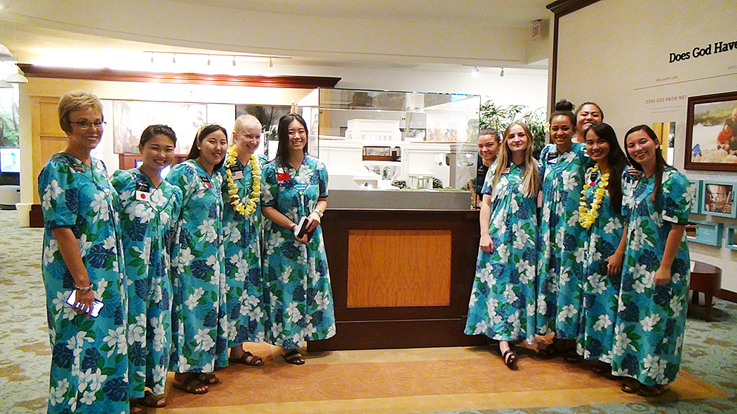 Sister missionaries serving in the Laie Hawaii Temple Visitors' Center pose next to the new cut-away model of the temple. They are required to wear Hawaiian-style muumuus as their uniforms while serving in the visitors' center, but otherwise wear more typical missionary apparel during their outside assignments. Many of them speak at least one language other than English.