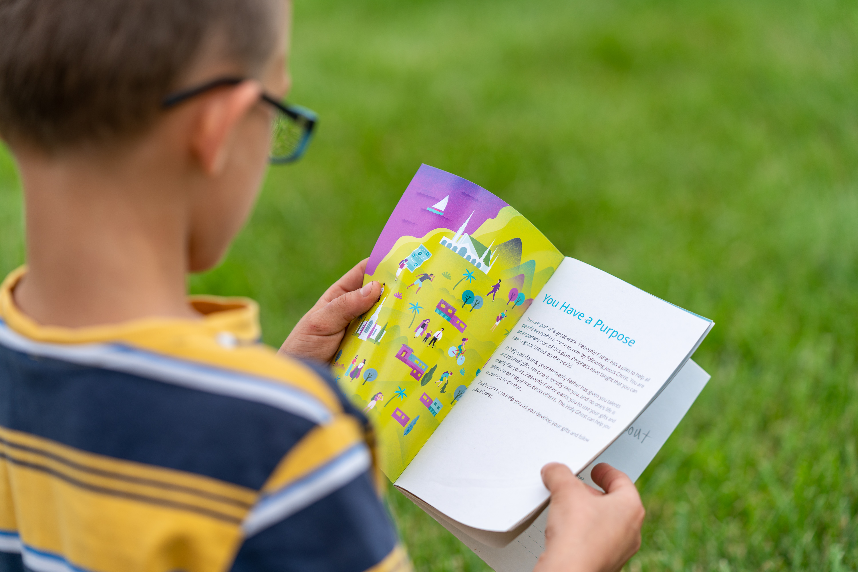 A young boy looks at a children's personal development guidebook for the new Children and Youth program.