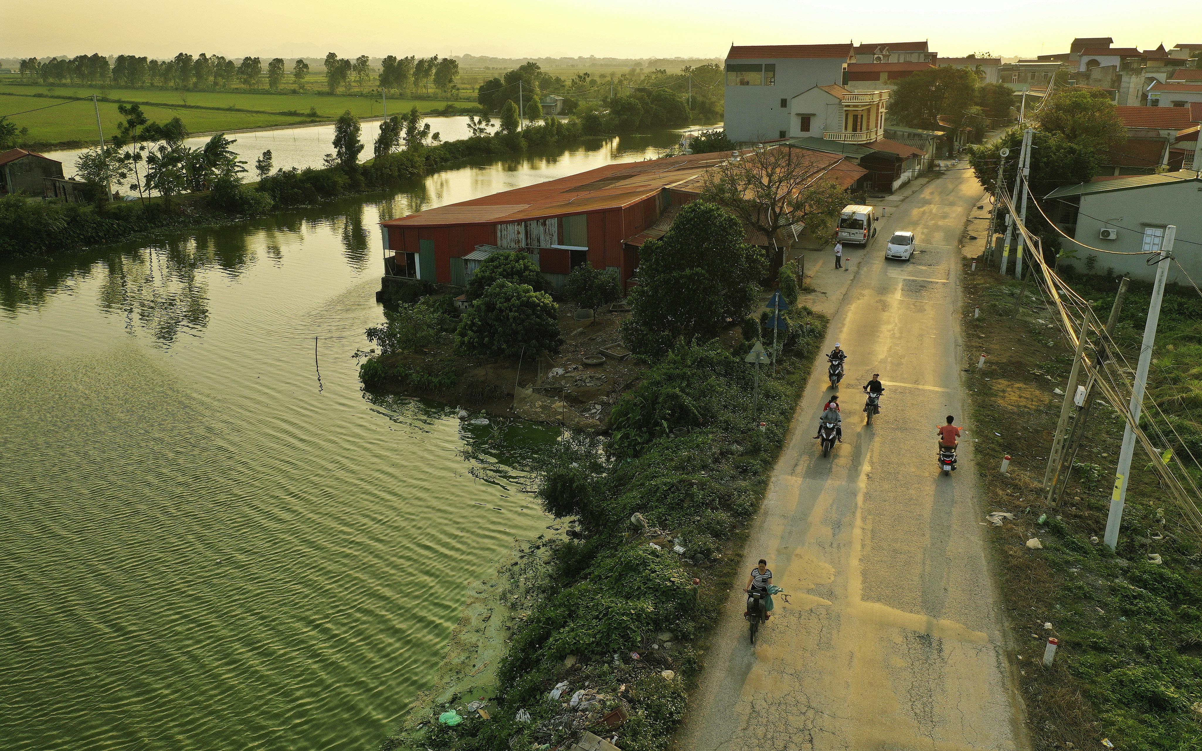 Motorists travel near the water in Hanoi, Vietnam, on Saturday, Nov. 16, 2019.