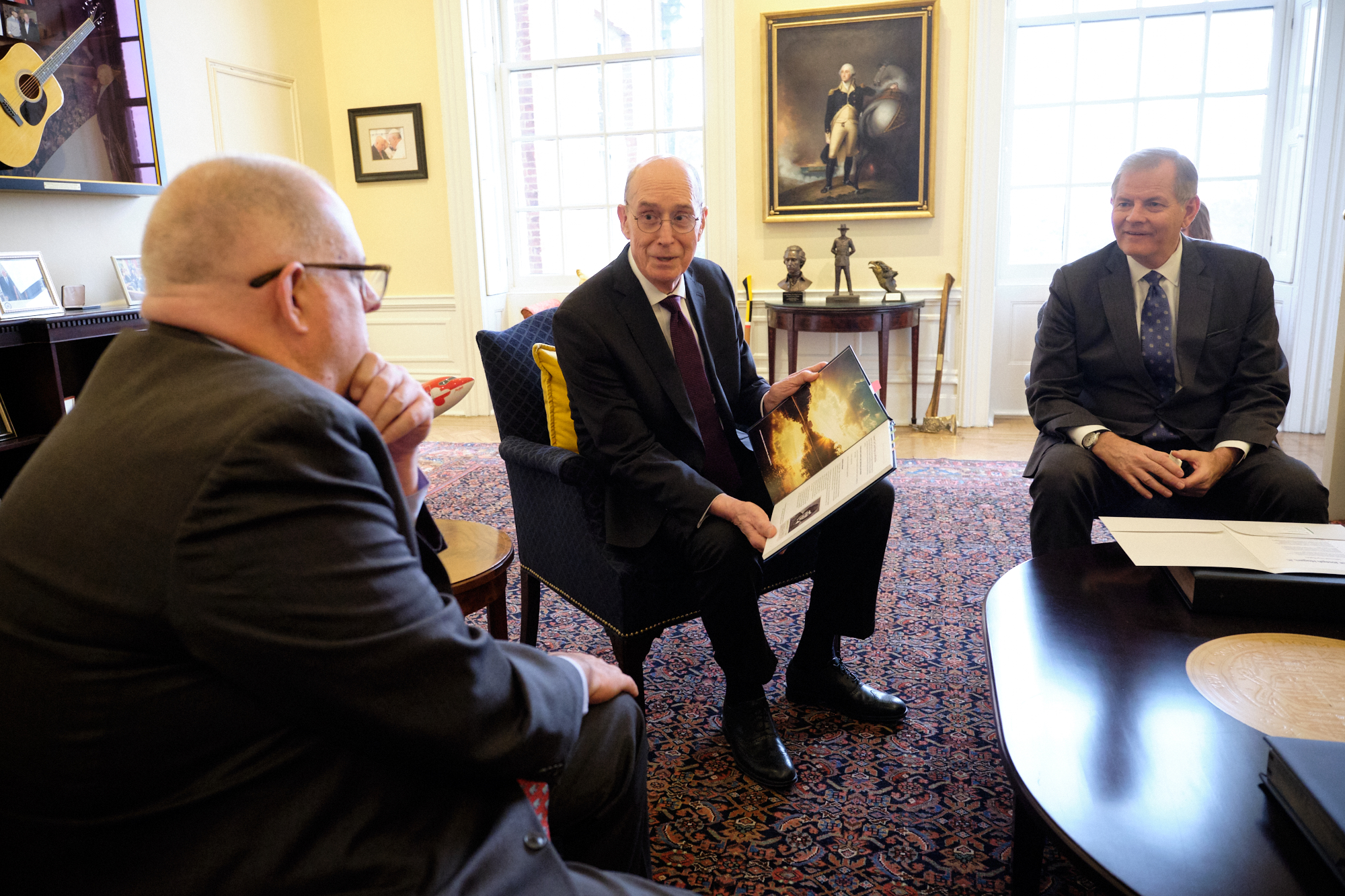 President Henry B. Eyring, center, and Elder Gary E. Stevenson present a personal family history to Maryland Governor Larry Hogan on Nov. 15, 2019.