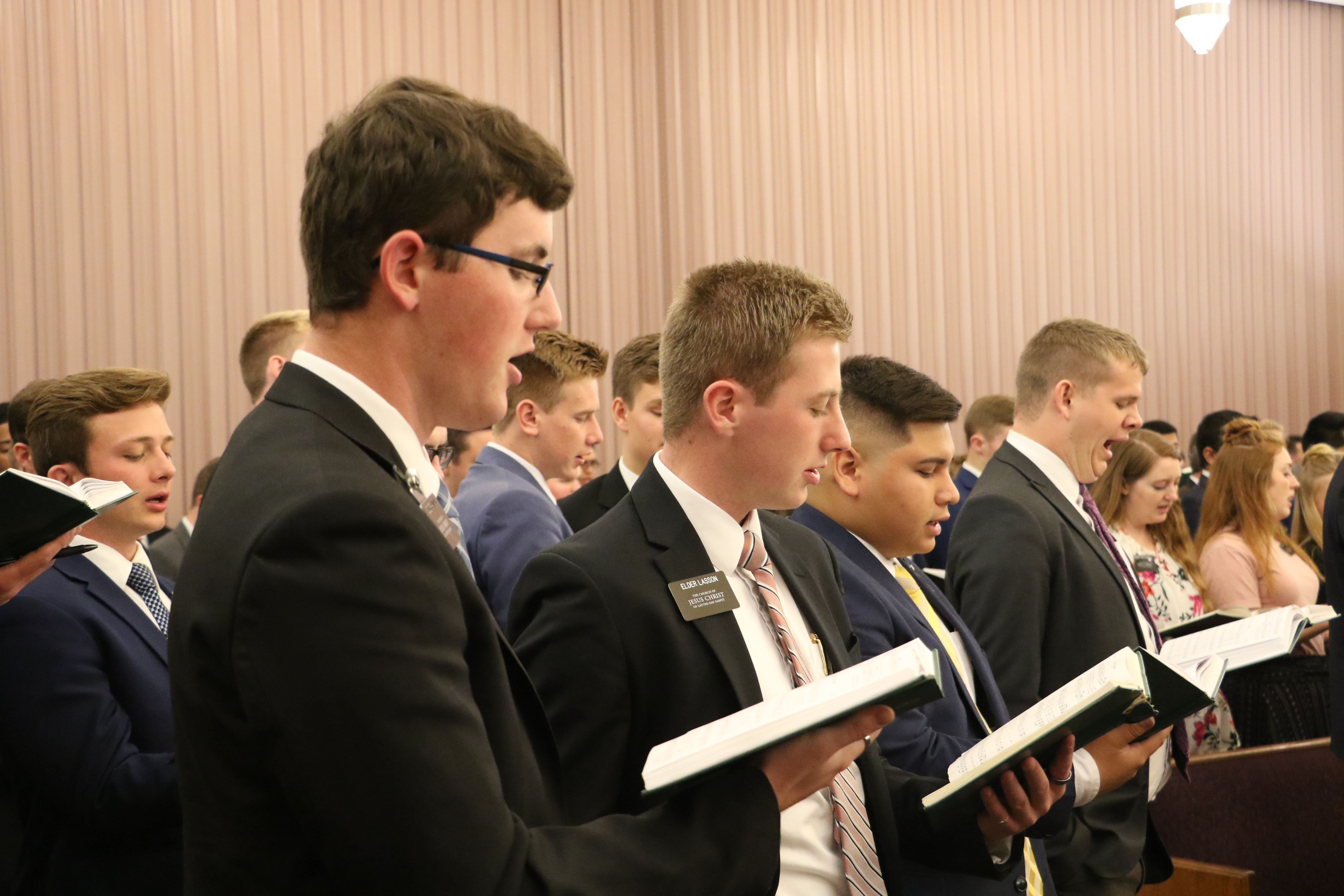 Missionaries serving in the Louisiana Baton Rouge Mission stand and sing under the direction of Sister Mary Cook during a devotional with Elder Quentin L. Cook of the Quorum of the Twelve Apostles on Saturday, Nov. 16, 2019, in Baton Rouge, Louisiana.