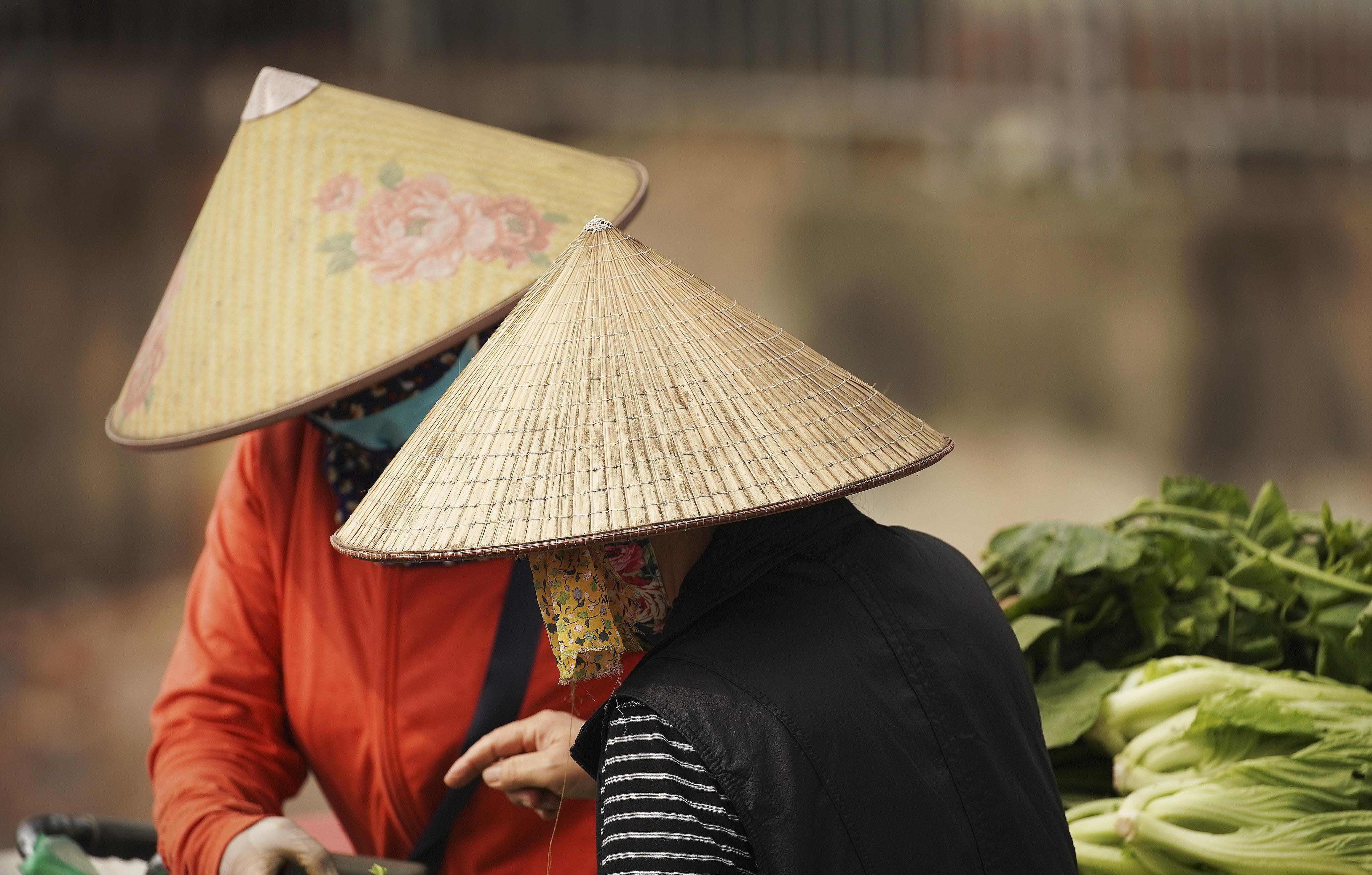 Women sell produce on the street in Hanoi, Vietnam on Saturday, Nov. 16, 2019.