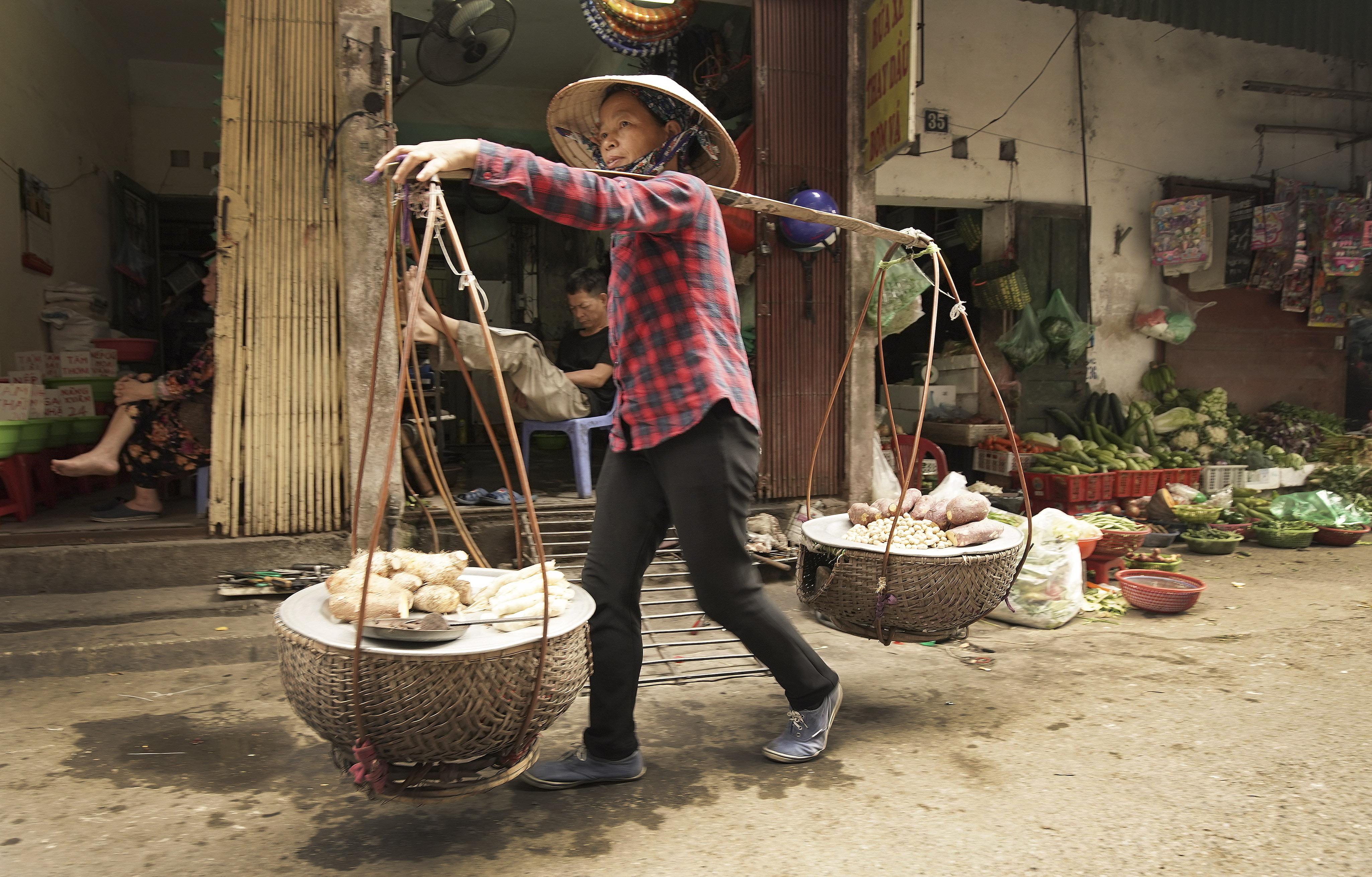 A woman sells produce in Hanoi, Vietnam on Saturday, Nov. 16, 2019.