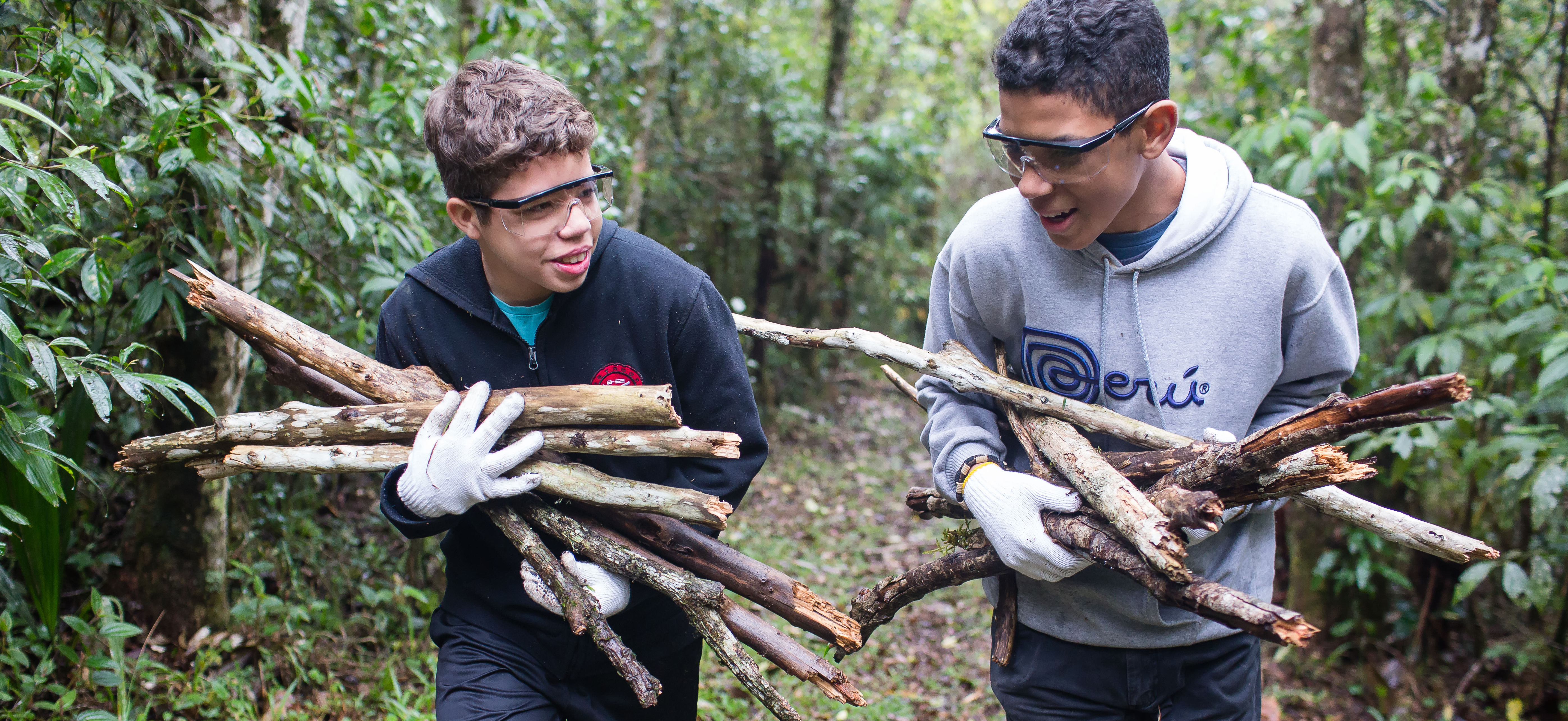 Young men carry sticks during a camping trip. A new camp guide for Aaronic Priesthood quorums has been released.