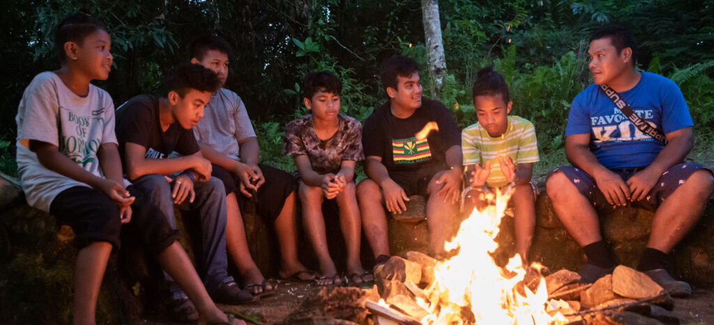 Young men and leaders sit around a campfire. A new camp guide for Aaronic Priesthood quorums has been released.
