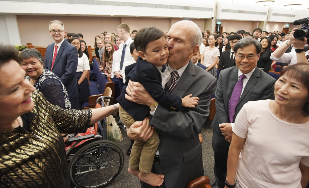 President Russell M. Nelson of The Church of Jesus Christ of Latter-day Saints kisses Tate Chan, 3, after a devotional in Singapore on Nov. 20, 2019.