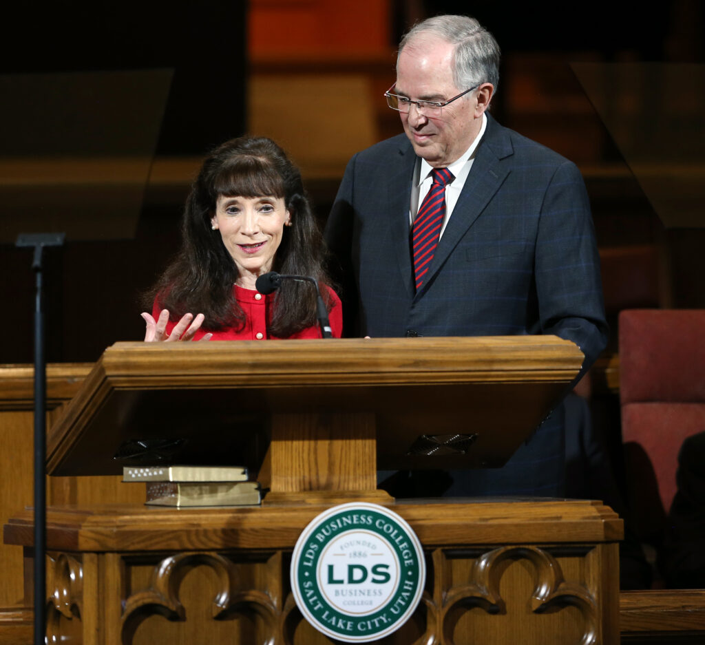 Sister Kathy Andersen tells a story from their family as she joins her husband, Elder Neil L. Andersen, at an LDS Business College devotional at the Assembly Hall on Temple Square on Tuesday, Nov. 19, 2019.