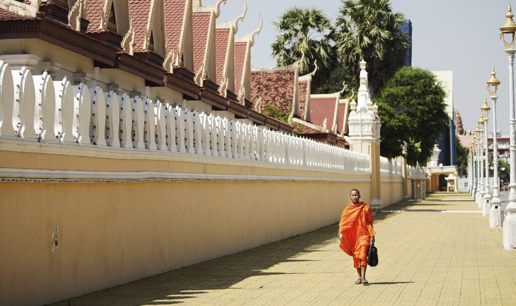 A Buddhist monk walks by the Royal Palace in Phnom Penh, Cambodia, on Nov. 19, 2019.