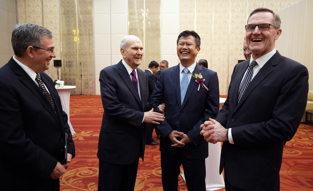 President Russell M. Nelson, second from left, of The Church of Jesus Christ of Latter-day Saints, laughs while talking with General Meach Sophana, secretary of state, in Phnom Penh, Cambodia, on Tuesday, Nov. 19, 2019. At left is Elder David F. Evans, a General Authority Seventy and Asia Area president. At right is Elder Peter F. Meurs, a General Authority Seventy serving in the Asia Area presidency.