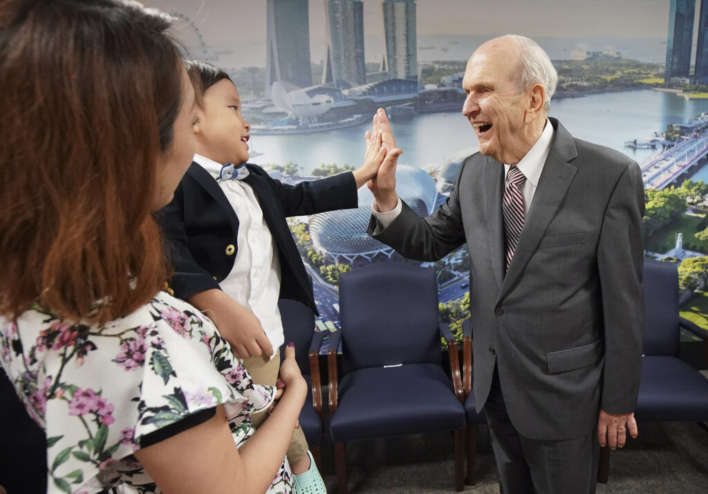 President Russell M. Nelson of The Church of Jesus Christ of Latter-day Saints high-fives Tate Chan, 3, while meeting with a three-generation family in Singapore on Nov. 20, 2019.