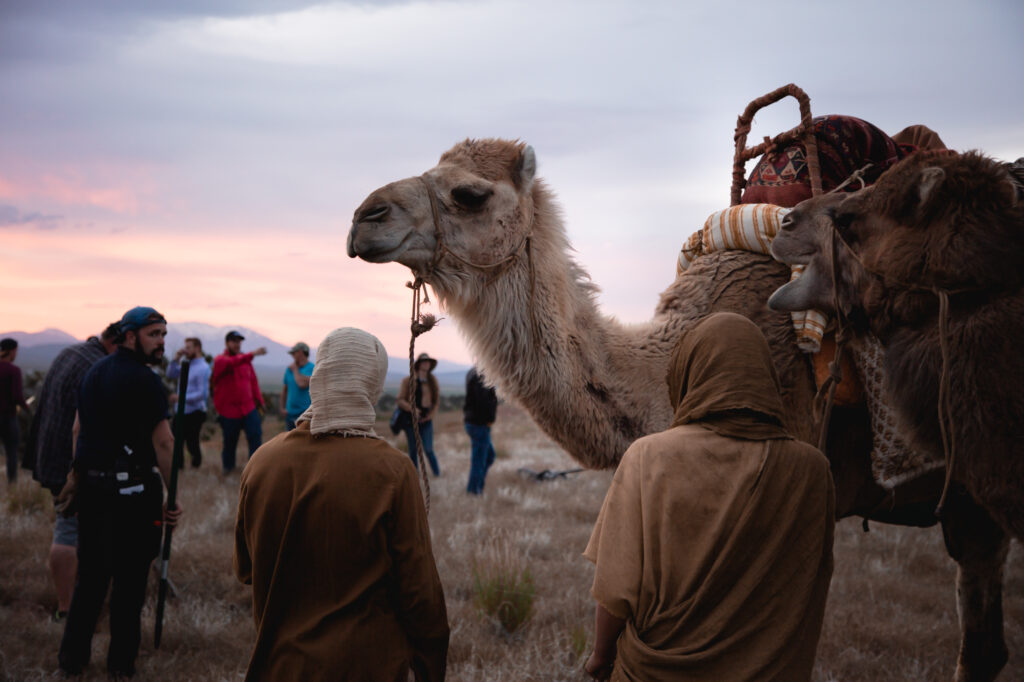 "A behind the scenes look at the filming of ""The Christ Child"" shows a camel and actors dressed in attire appropriate for first century Israel."