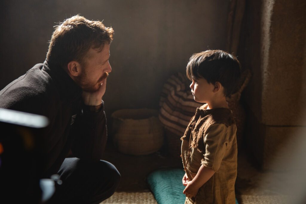 "A behind the scenes look at the filming of ""The Christ Child"" shows a moment with the director and the child playing a young Jesus."