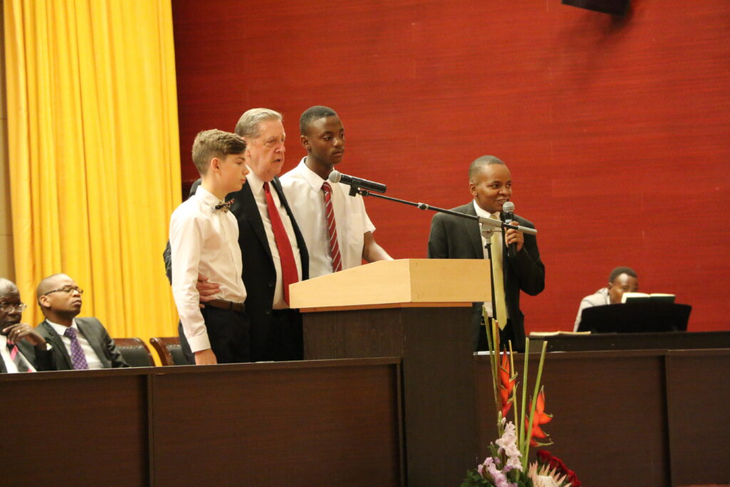 Elder Jeffrey R. Holland of the Quorum of the Twelve Apostles stands next to two young men at the podium as he speaks during a multi-stake conference at the Joaquim Chissano International Conference Center in Maputo, Mozambique, on Sunday, Nov. 17, 2019.