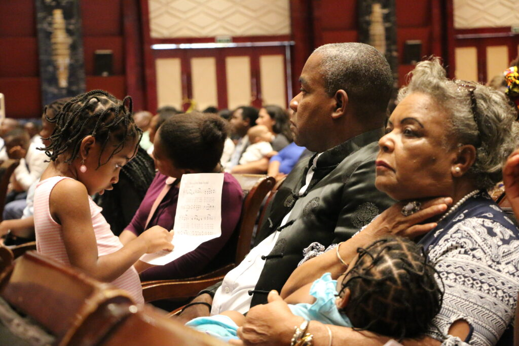 A family listens to Elder Jeffrey R. Holland of the Quorum of the Twelve Apostles speak during a multi-stake conference at theJoaquim Chissano International Conference Centerin Maputo, Mozambique, on Sunday, Nov. 17, 2019.