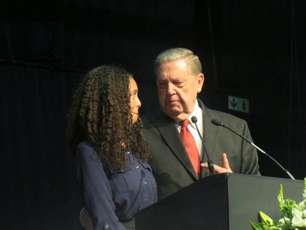 Elder Jeffrey R. Holland of the Quorum of the Twelve Apostles stands next to Judith Mahlangu, a recently returned missionary, at the pulpit during a multi-stake conference at theGallagher Convention Center near Johannesburg, South Africa, on Sunday, Nov. 10, 2019.