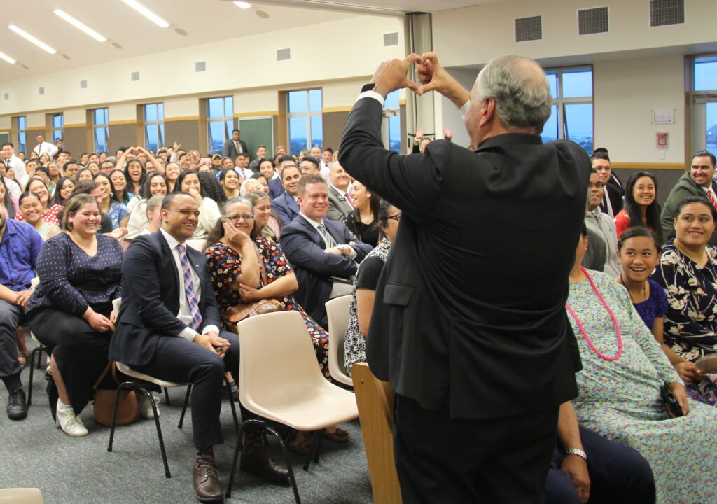 Forming a heart with his fingers, Elder Ronald A. Rasband bids farewell young single adults after speaking at a Nov. 17, 2019, devotional in Auckland, New Zealand.