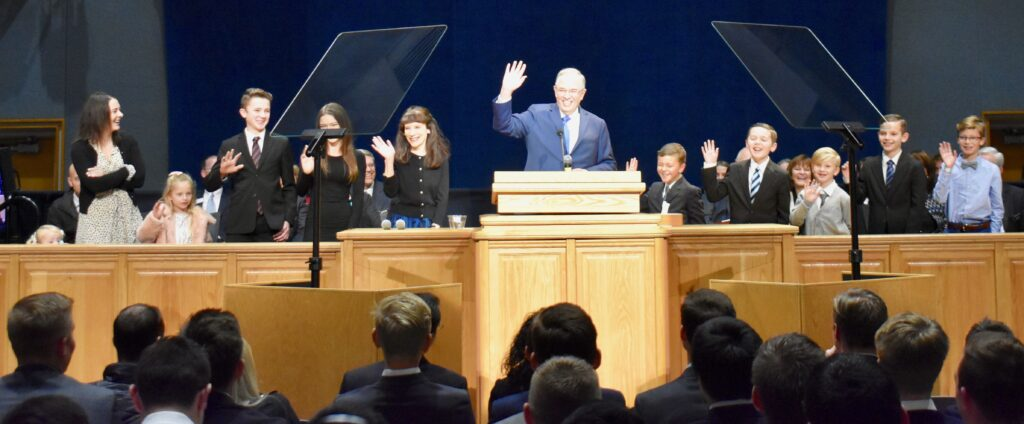 With 10 of their grandchildren, Elder Neil L. Andersen and his wife, Sister Kathy Andersen, wave as they greet missionaries not only at the Provo Missionary Training Center during a Nov. 28, 2019, devotional but via the broadcast to other international MTCs.