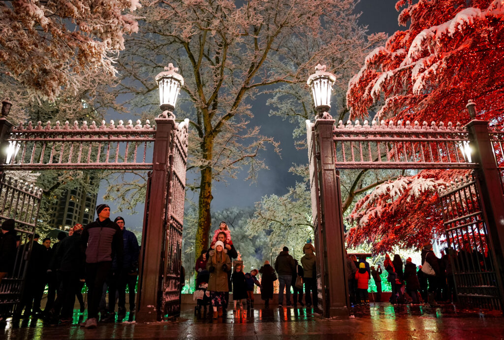 The gates of Temple Square are covered in snow as people enjoy the first night of the annual Christmas lights display at Temple Square in Salt Lake City on Friday, Nov. 29, 2019.