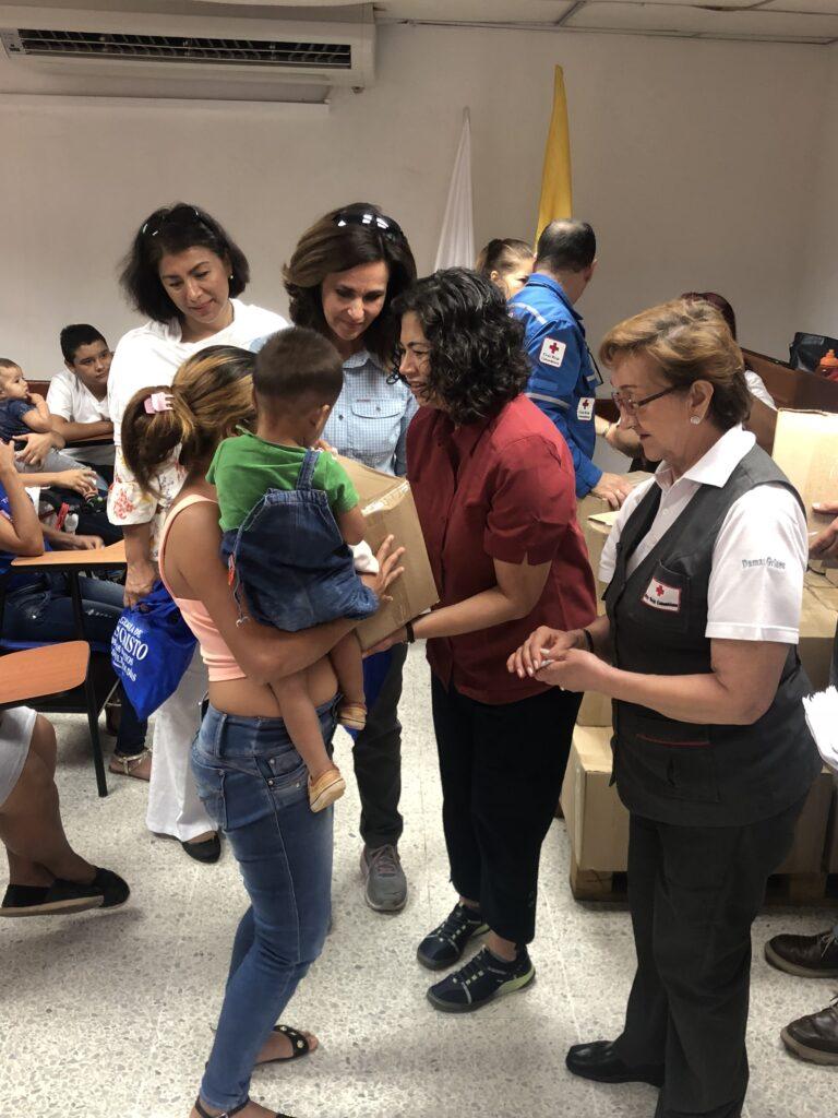 La Hermana Lisa L. Harkness, centro, y la Hermana Reyna I.Aburto, centro derecha, ayudan en un centro de ayuda de la Cruz Roja cerca de la frontera de Venezuela en Colombia durante un viaje al Área Sudoccidental de la Iglesia en Sudamérica en noviembre de 2019.