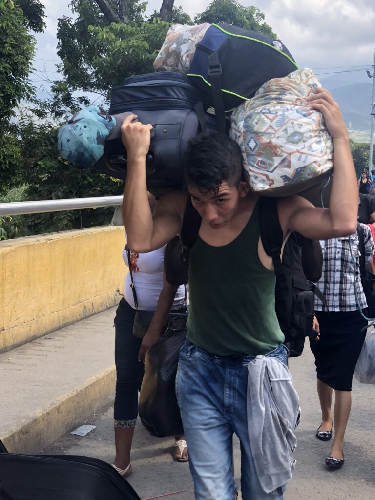 Refugees and volunteers carry personal belongings and supplies across the border between Venezuela and Colombia in Nov. 2019.