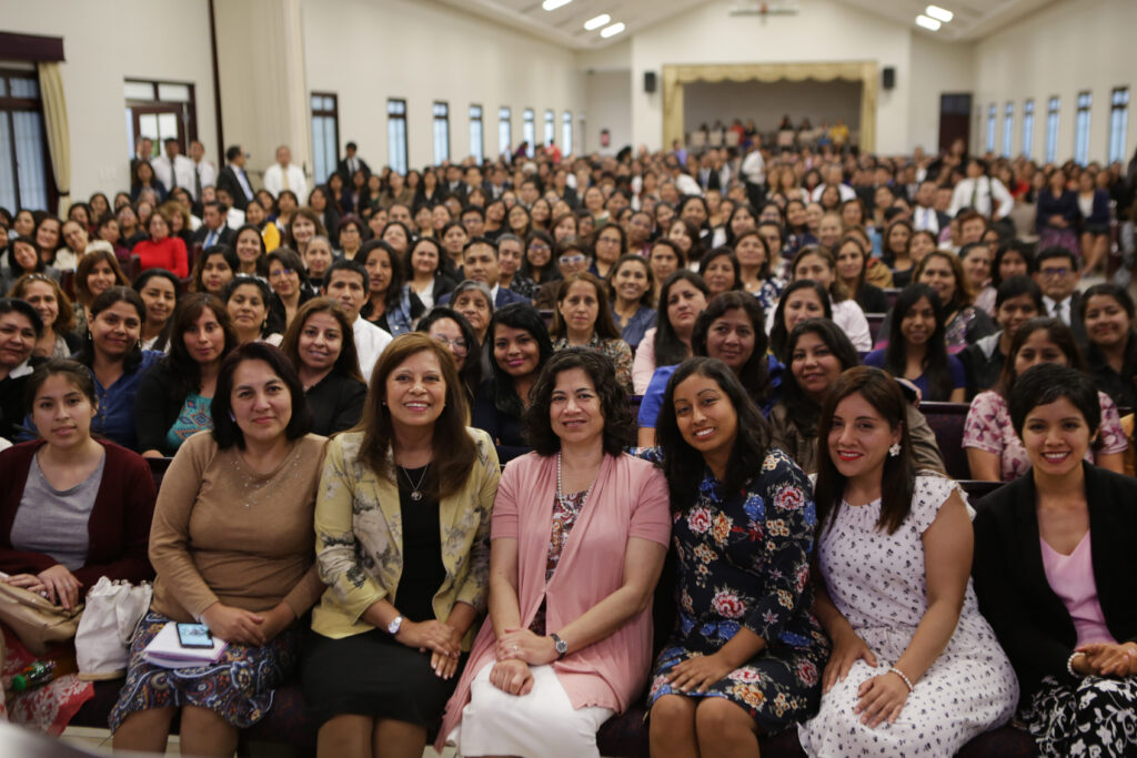 Sister Reyna I. Aburto, center, sits for a photo with members of the church in Lima, Peru, after a leadership meeting during a visit to the South America Northwest Area of the Church in November 2019.