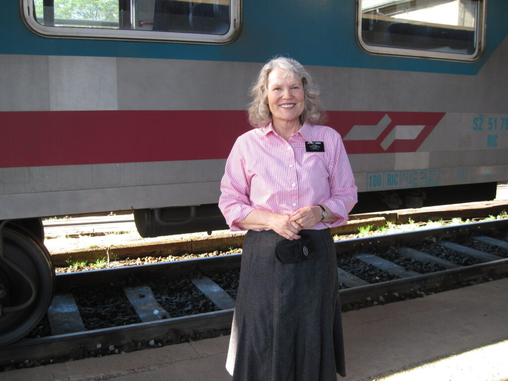 Sister Joan Turner poses next to a train while traveling to Maribor, Slovenia.