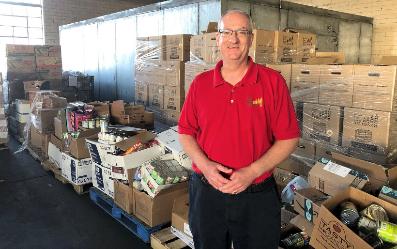 Dan Maher, President and CEO of Southeast Texas Food Bank in Beaumont, Texas, stands near a donation from the Church in November 2019.