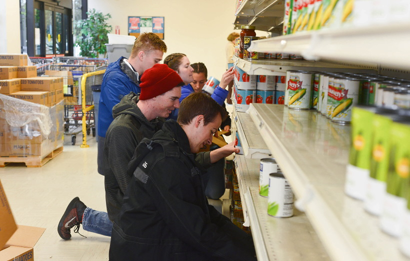 Missionaries from the Texas Houston Mission restock the shelves at Northwest Assistance Ministries with food supplies from a Church donation onNov. 13, 2019.
