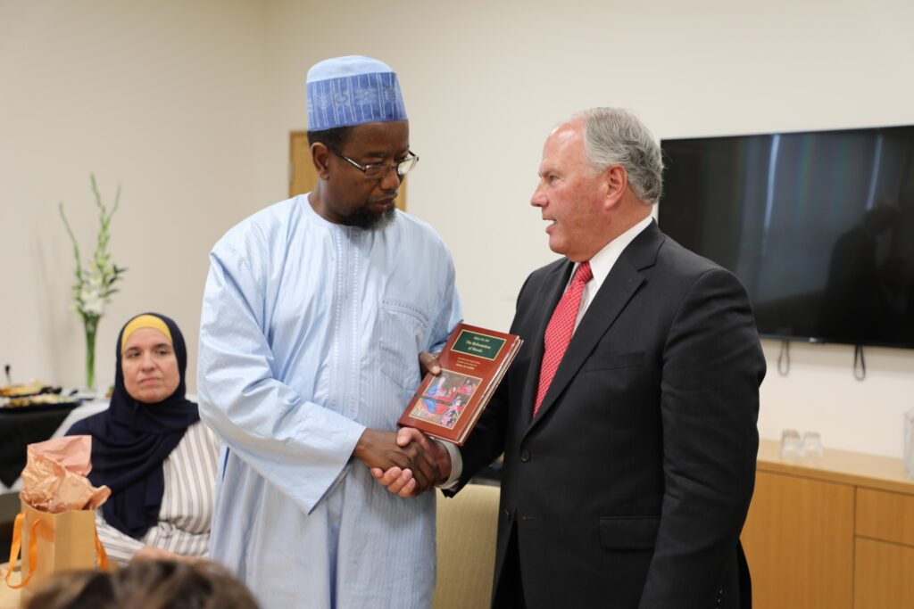 Dr. Mustafa Farouk, president of the Federation of Islamic Associations of New Zealand, receives a book from Elder Ronald A. Rasband in a Nov. 16, 2019, meeting in Hamilton, New Zealand.