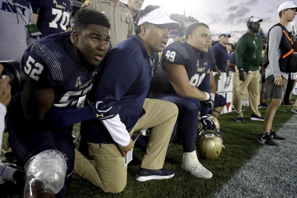 Navy head coach Ken Niumatalolo, center, kneel with defensive end Denzel Polk (52) and defensive lineman Jackson Pittman (99) as they watch the final play of an NCAA college football game against Air Force Saturday, Oct. 5, 2019, in Annapolis, Md. Navy won 34-25.