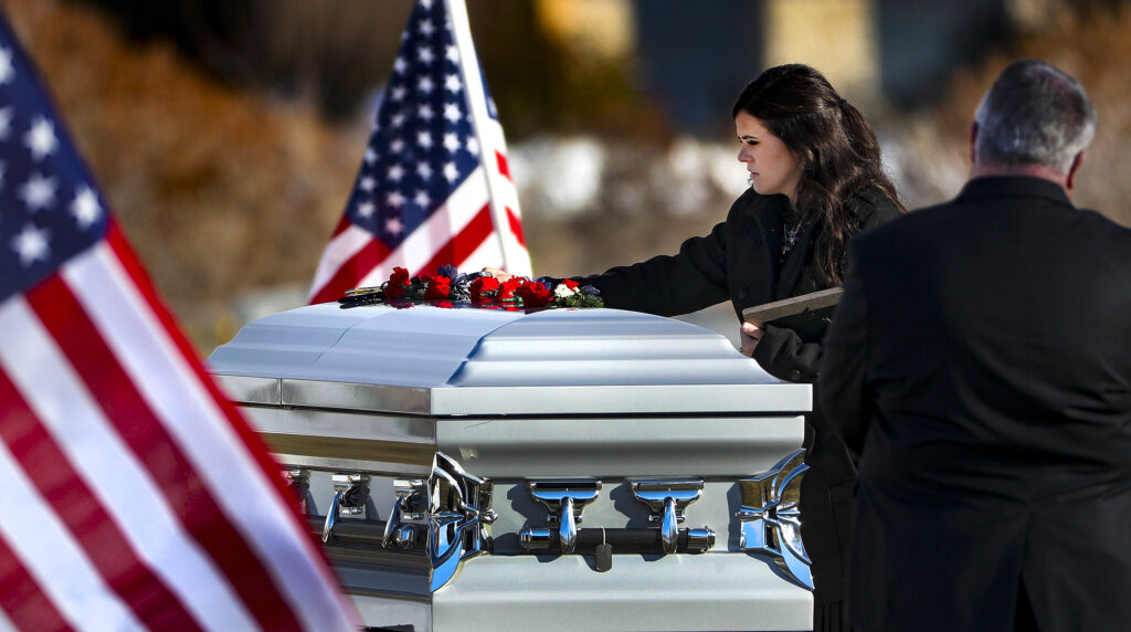 McKenzie Norman Fuchigami, wife of Chief Warrant Officer 2 Kirk T. Fuchigami Jr., rests her hand on her husband's casket during graveside services at the Brigham City Cemetery on Monday, Dec. 9, 2019. Fuchigami and his co-pilot died when their helicopter crashed as they provided security for troops on the ground in Logar Province in eastern Afghanistan.