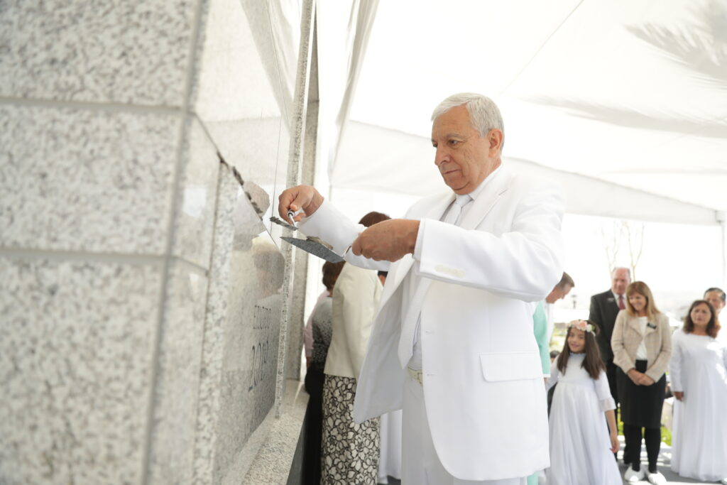 Elder Enrique R. Falabella carefully places mortar on the cornerstone of the Arequipa Peru Temple on Dec. 15, 2019.